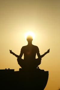 Photo of meditating person in front of the sun. Enlighten yourself by connecting with your very own Self - your Soul. Benefit from our free gift today.